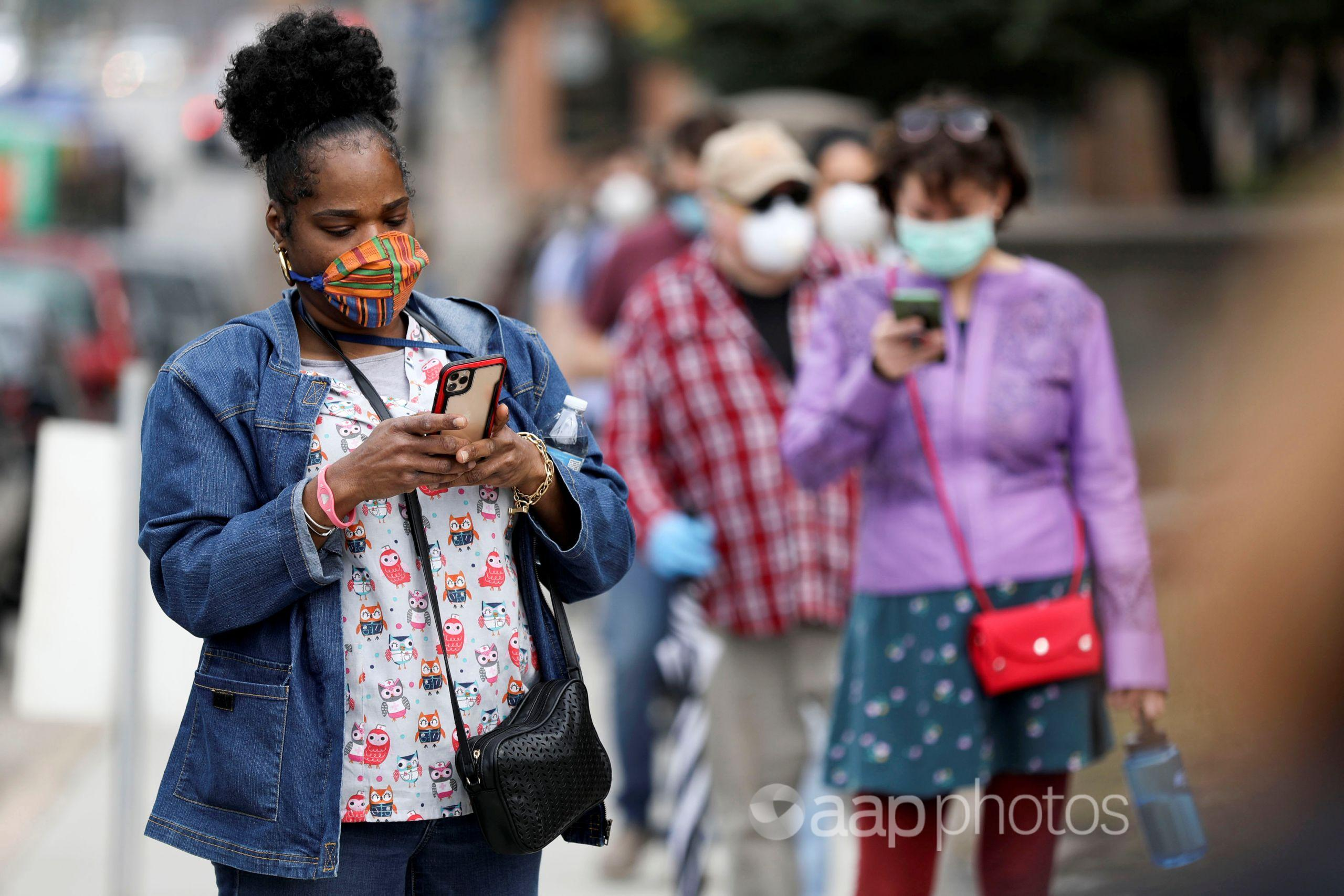 Woman in a mask using a mobile phone