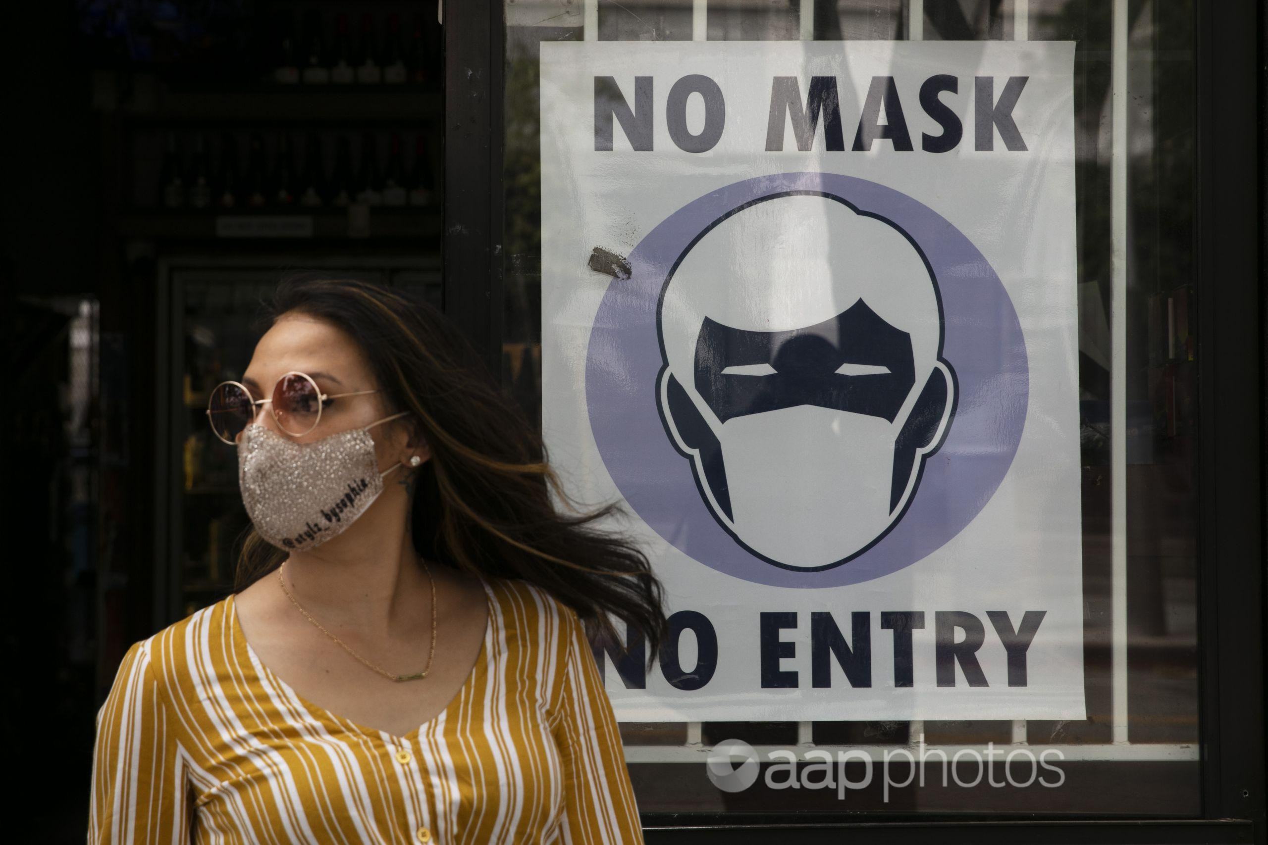 A woman walks past a sign requesting its customers to wear a mask.