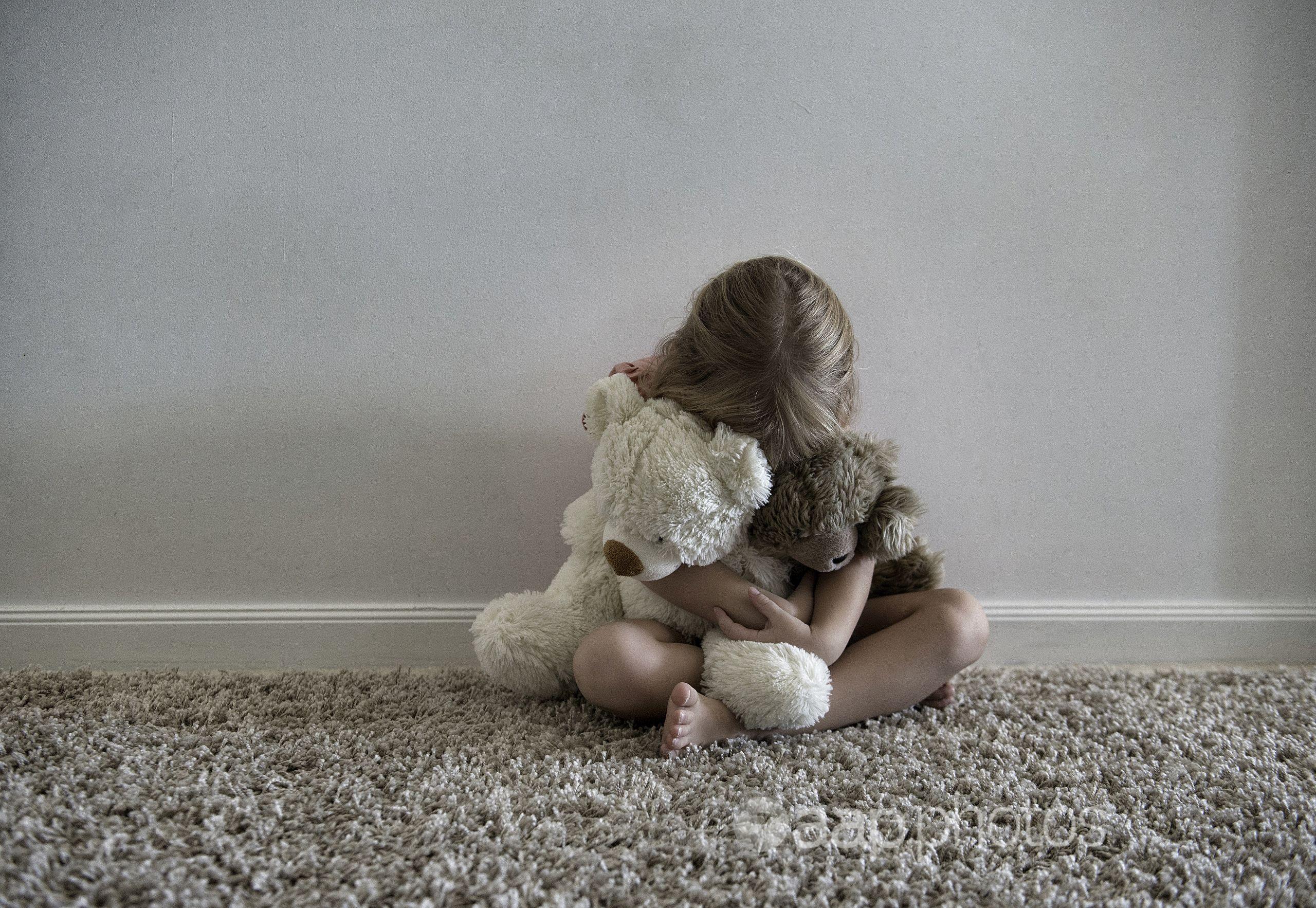 A little girl hugging toys.