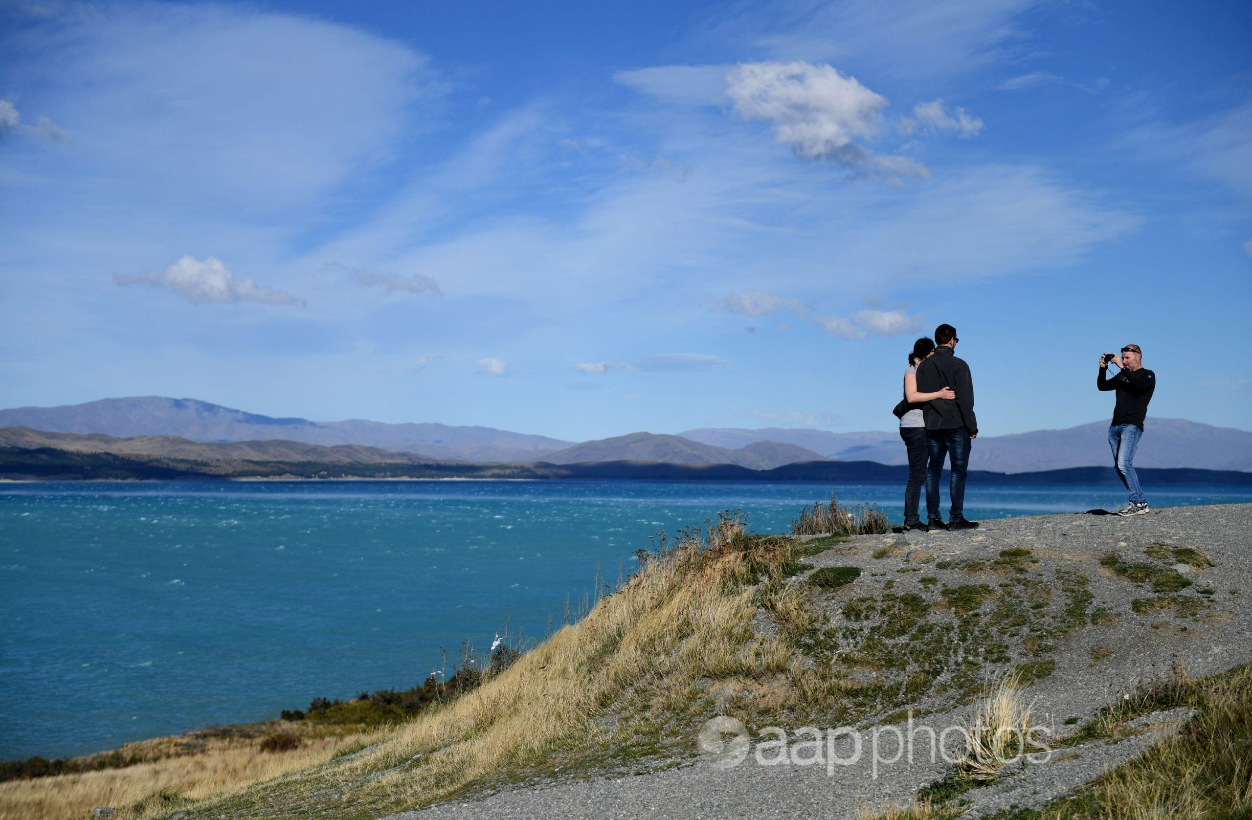 Couple has their photo taken on the shore of a lake in NZ