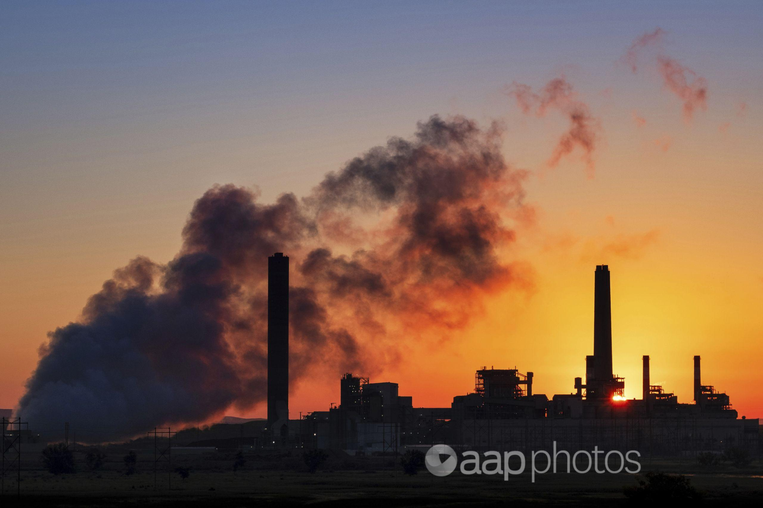 Coal-fired power station silhouetted at sunset