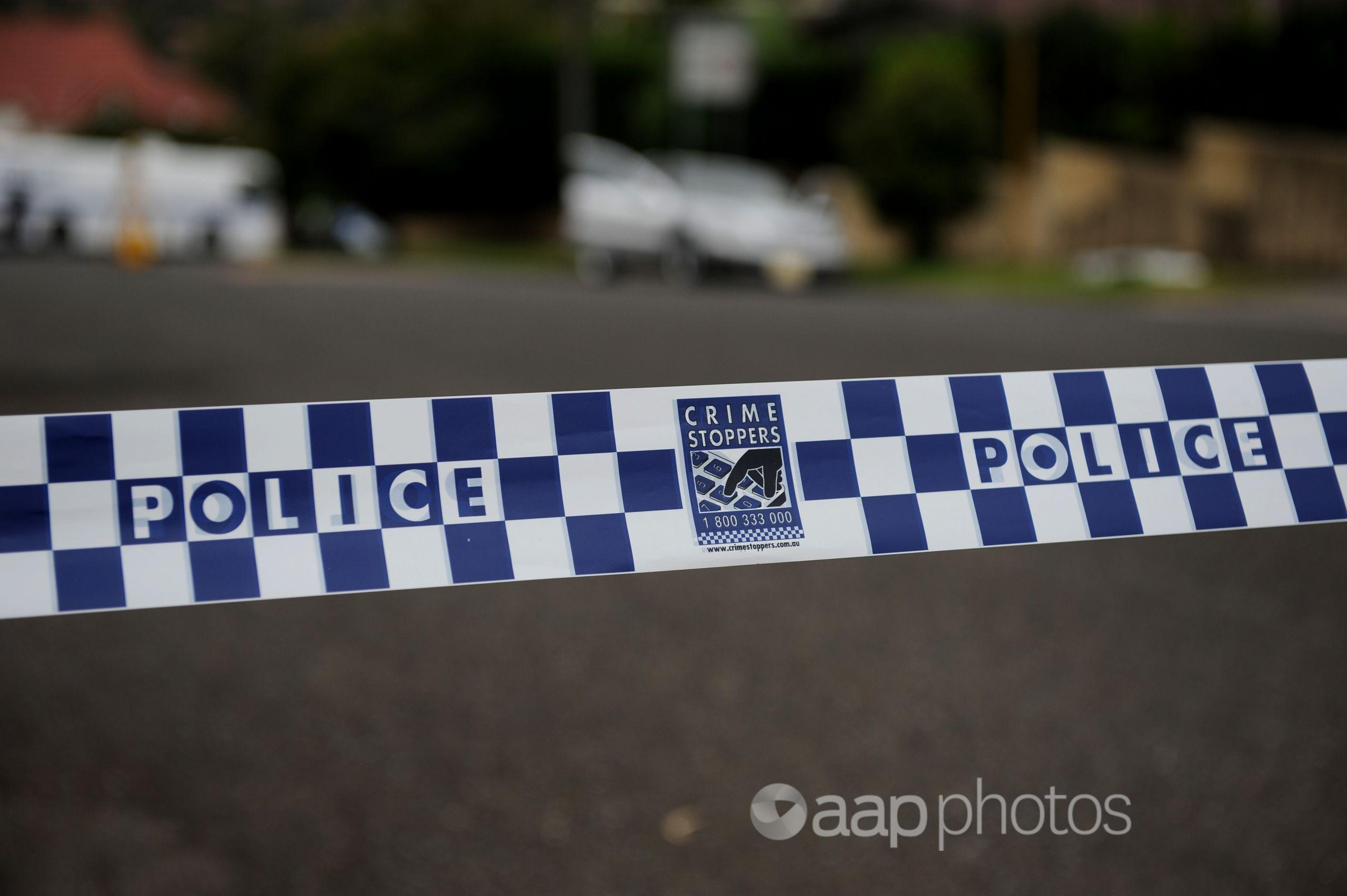 Police tape restricts access to a street.