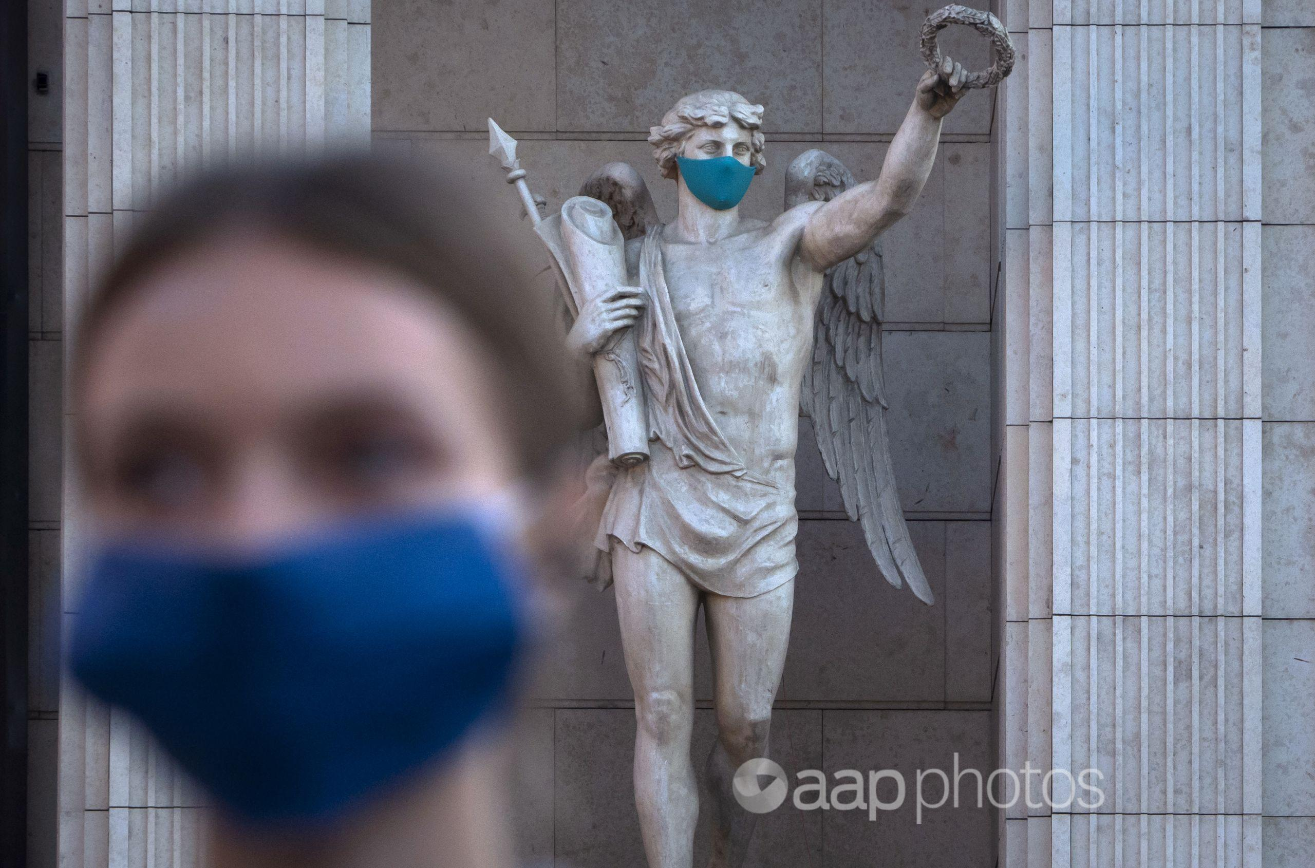 A woman wearing a face mask walks past a statue with a face mask.