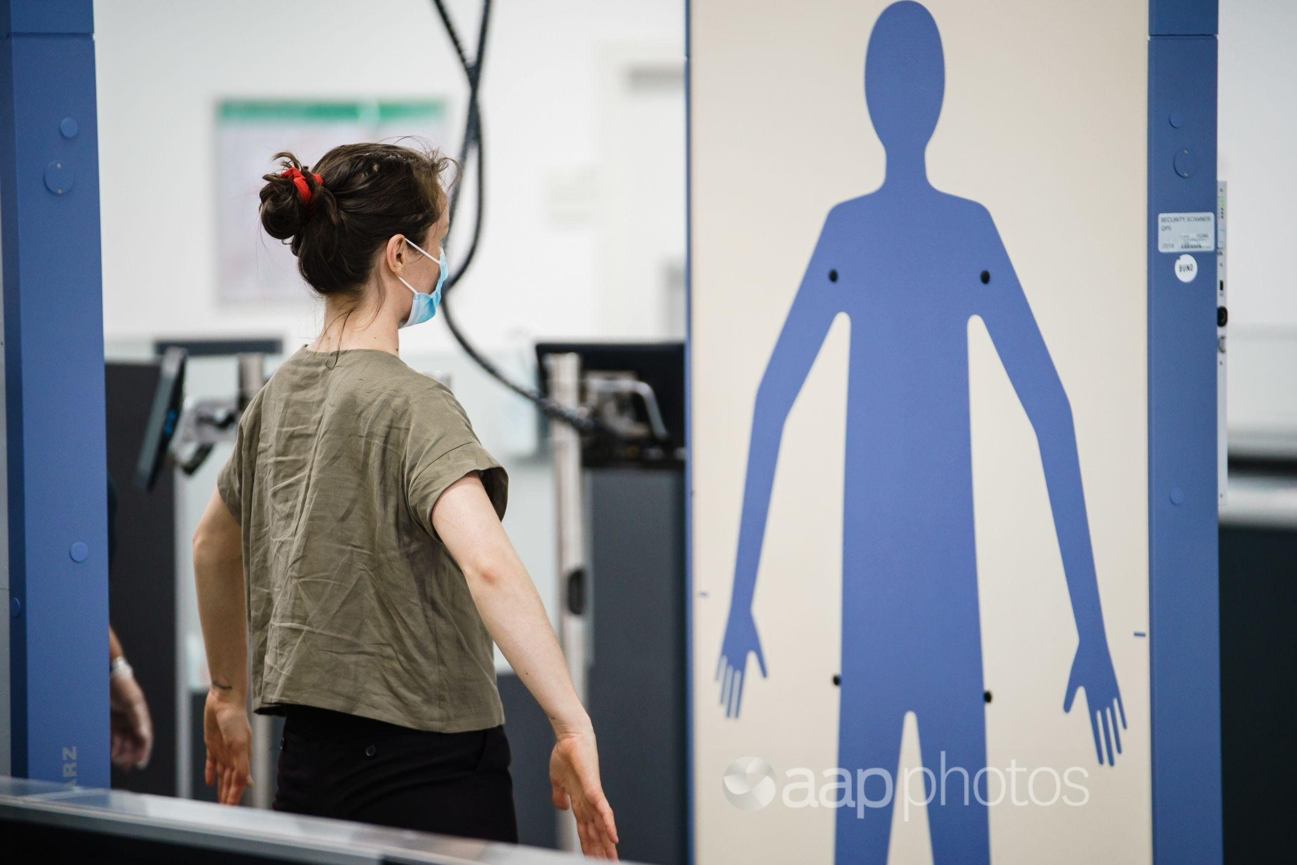 A passenger stands in a body scanner at an airport.