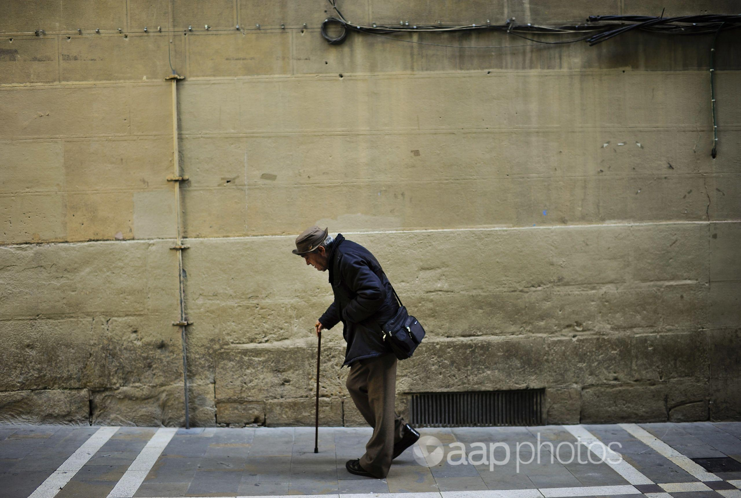 An elderly man goes for a walk aided by a walking-stick.