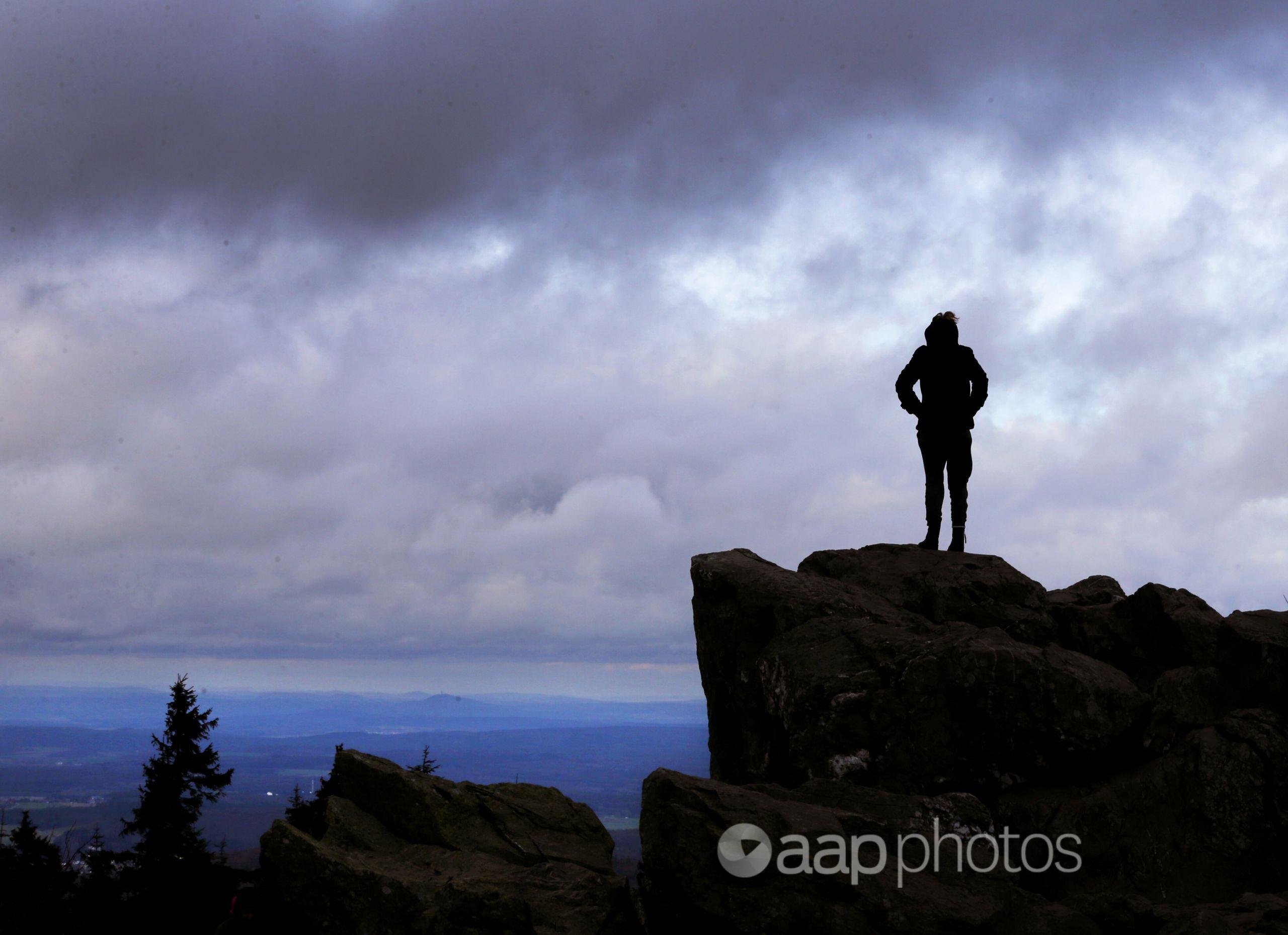 A woman stands on rocks on top of a mountain.