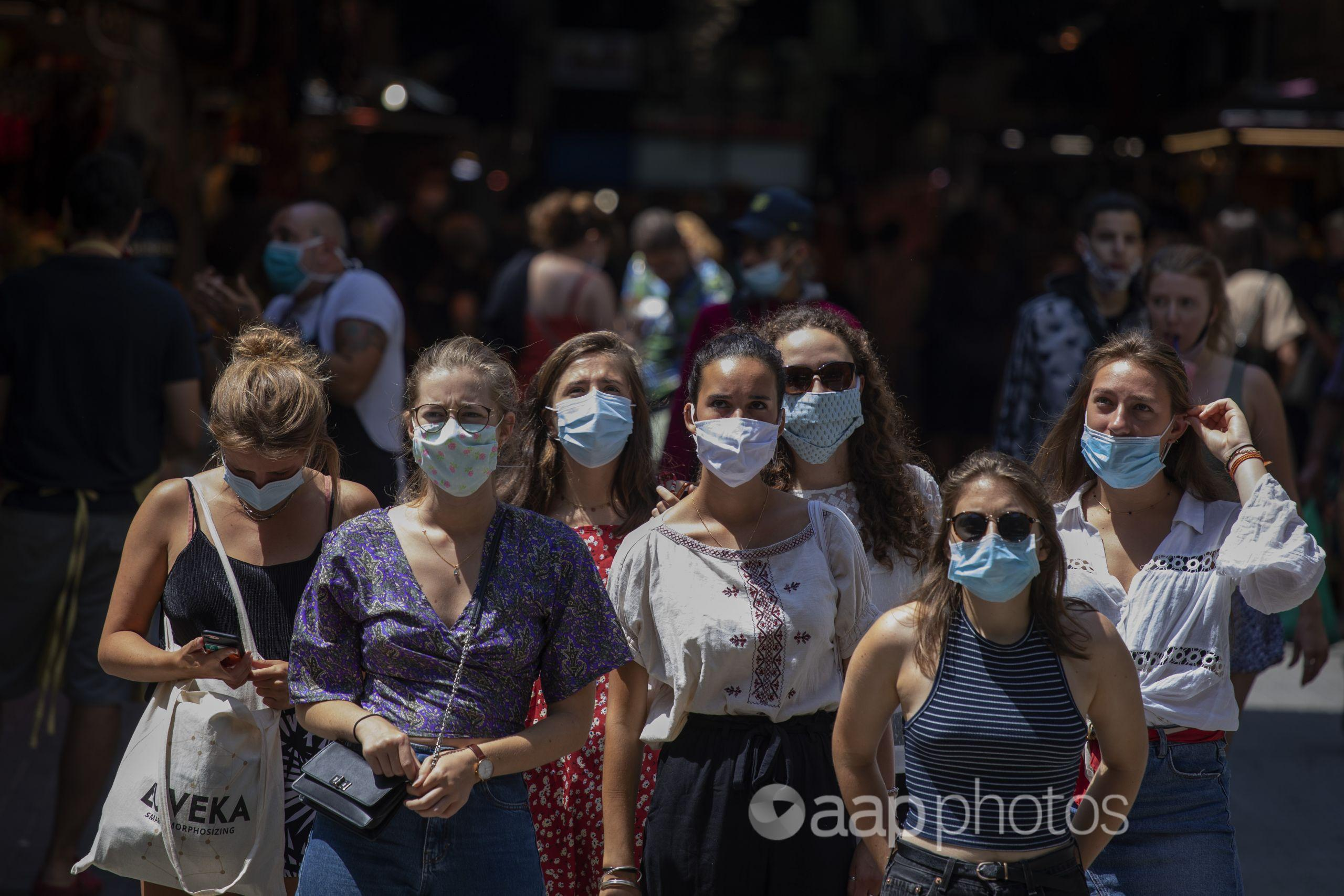 Tourists wearing face masks wait to cross a road in Barcelona.
