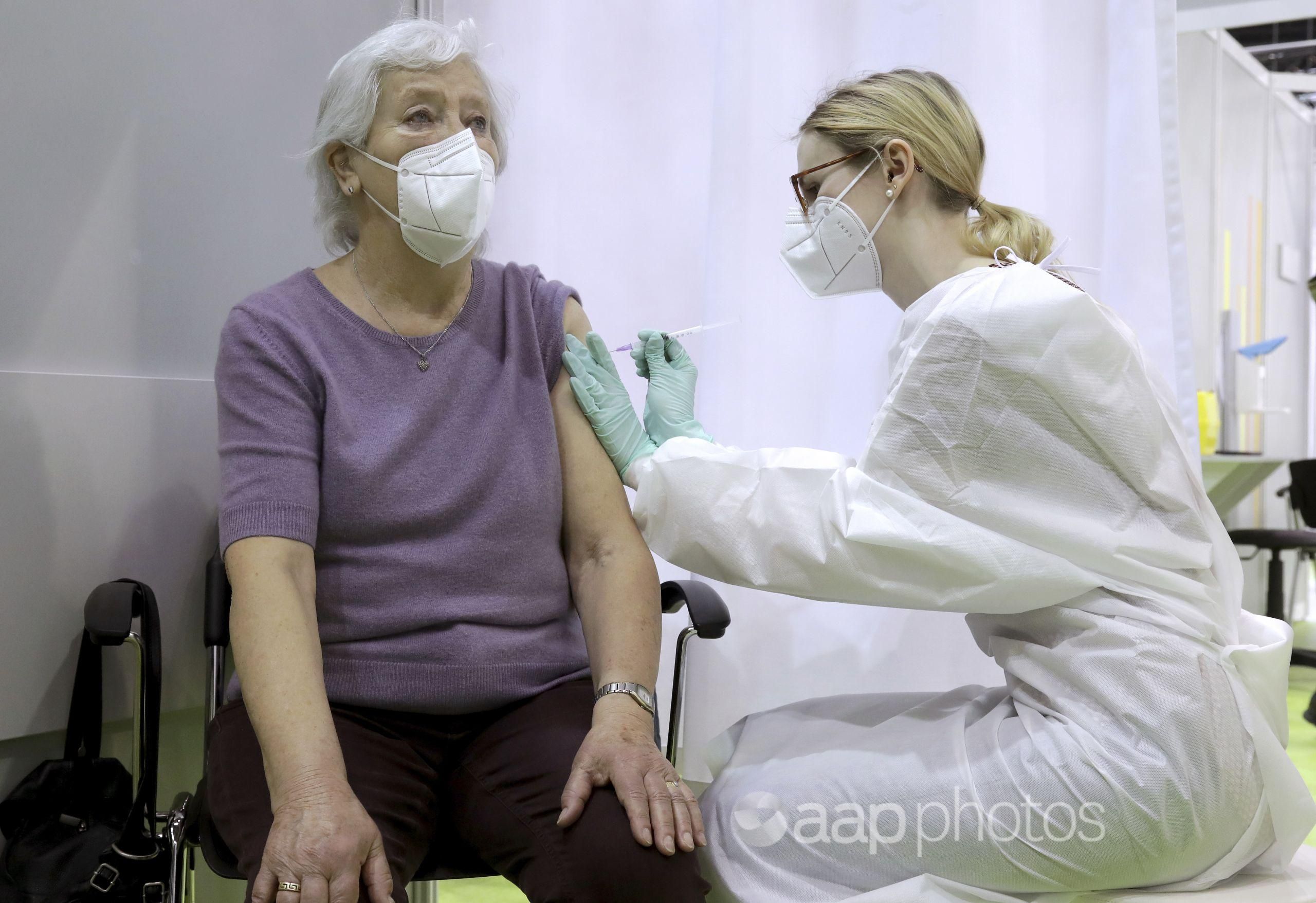 A woman receives a COVID-19 vaccination by a doctor.