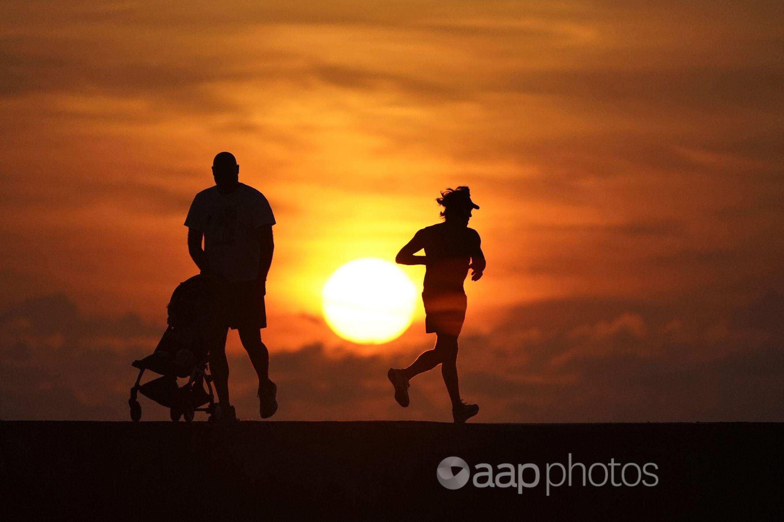 runner, man pushing pram silhouetted against a sunrise