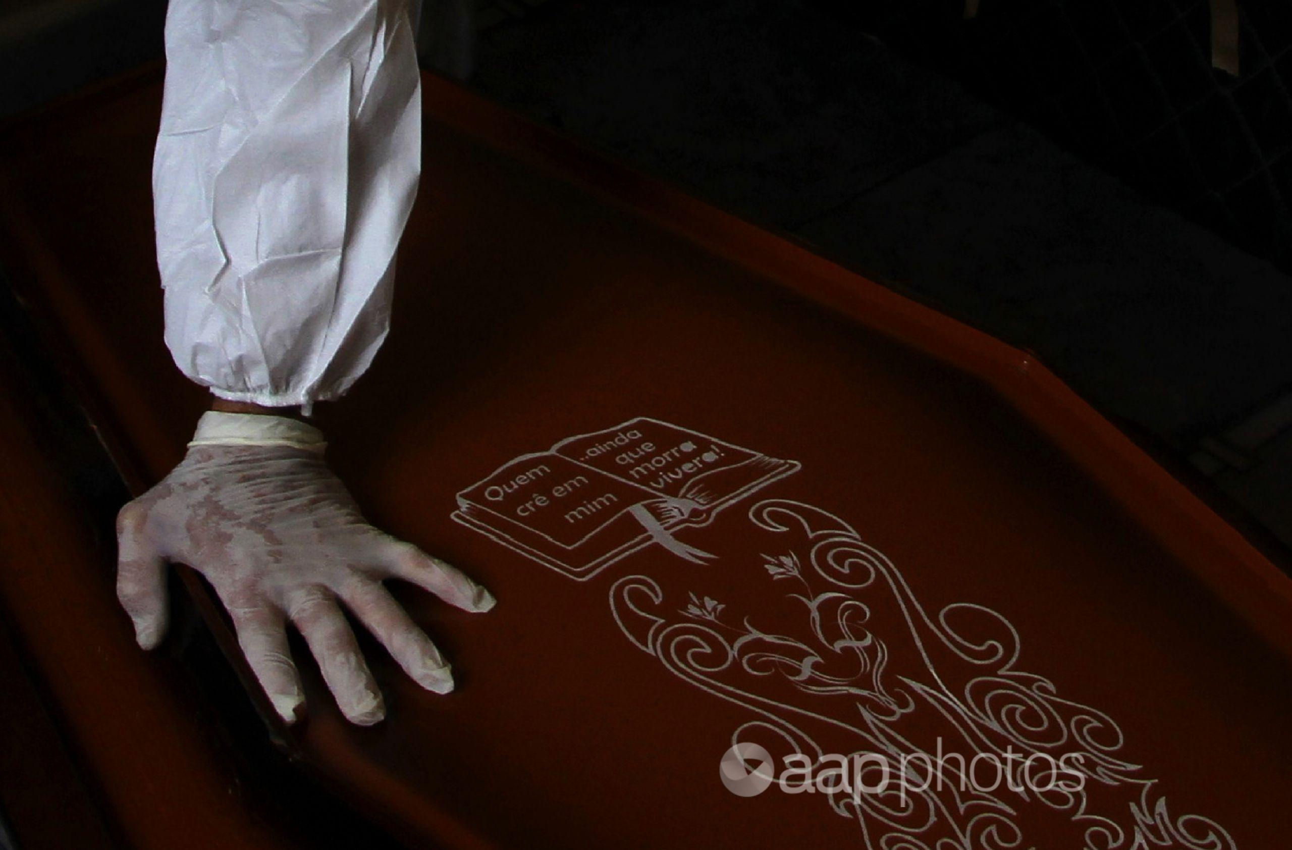 A person wearing PPE touches a coffin