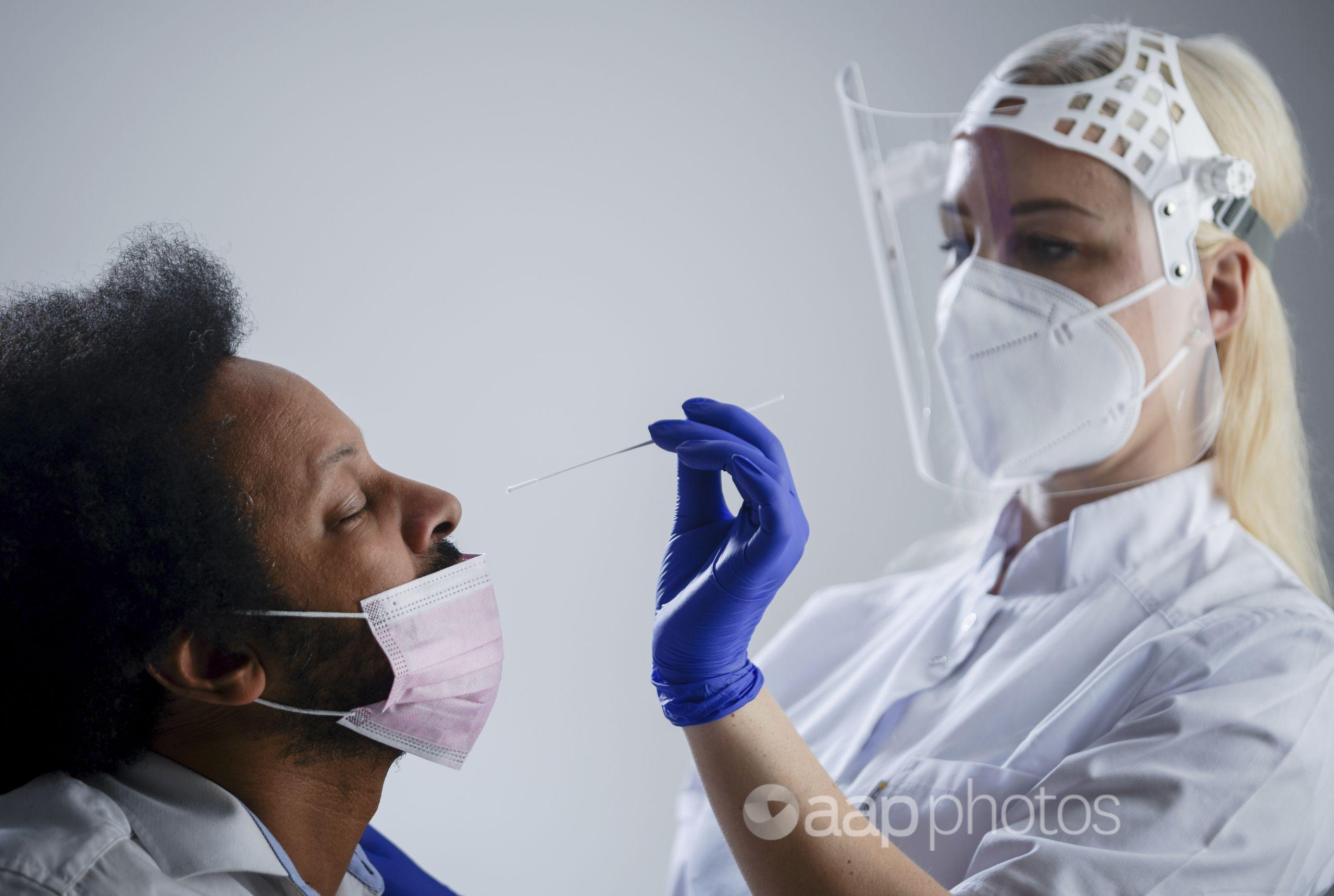 A nurse conducting a PCR COVID-19 test