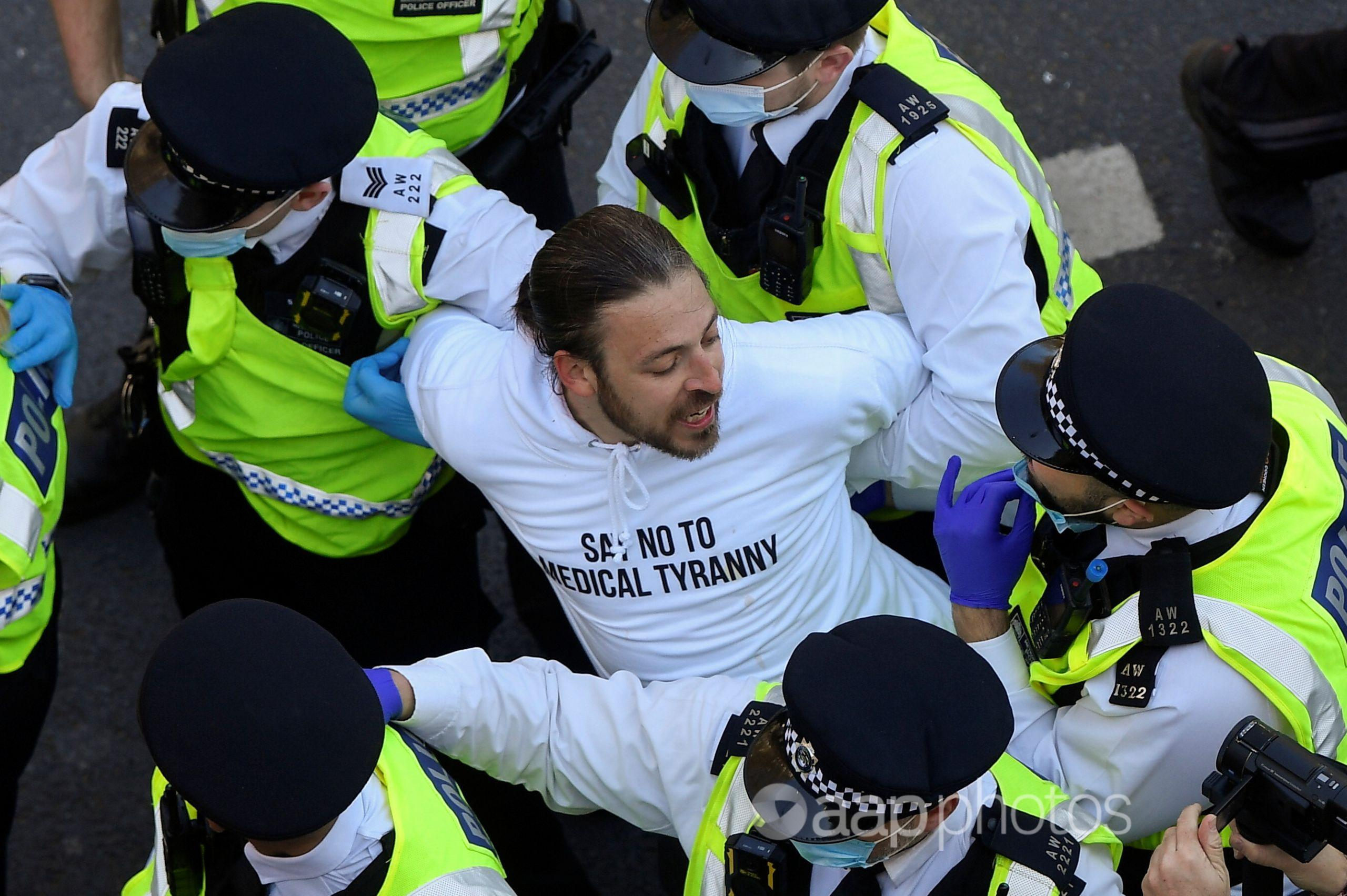 Police detain a demonstrator during the anti-lockdown protest