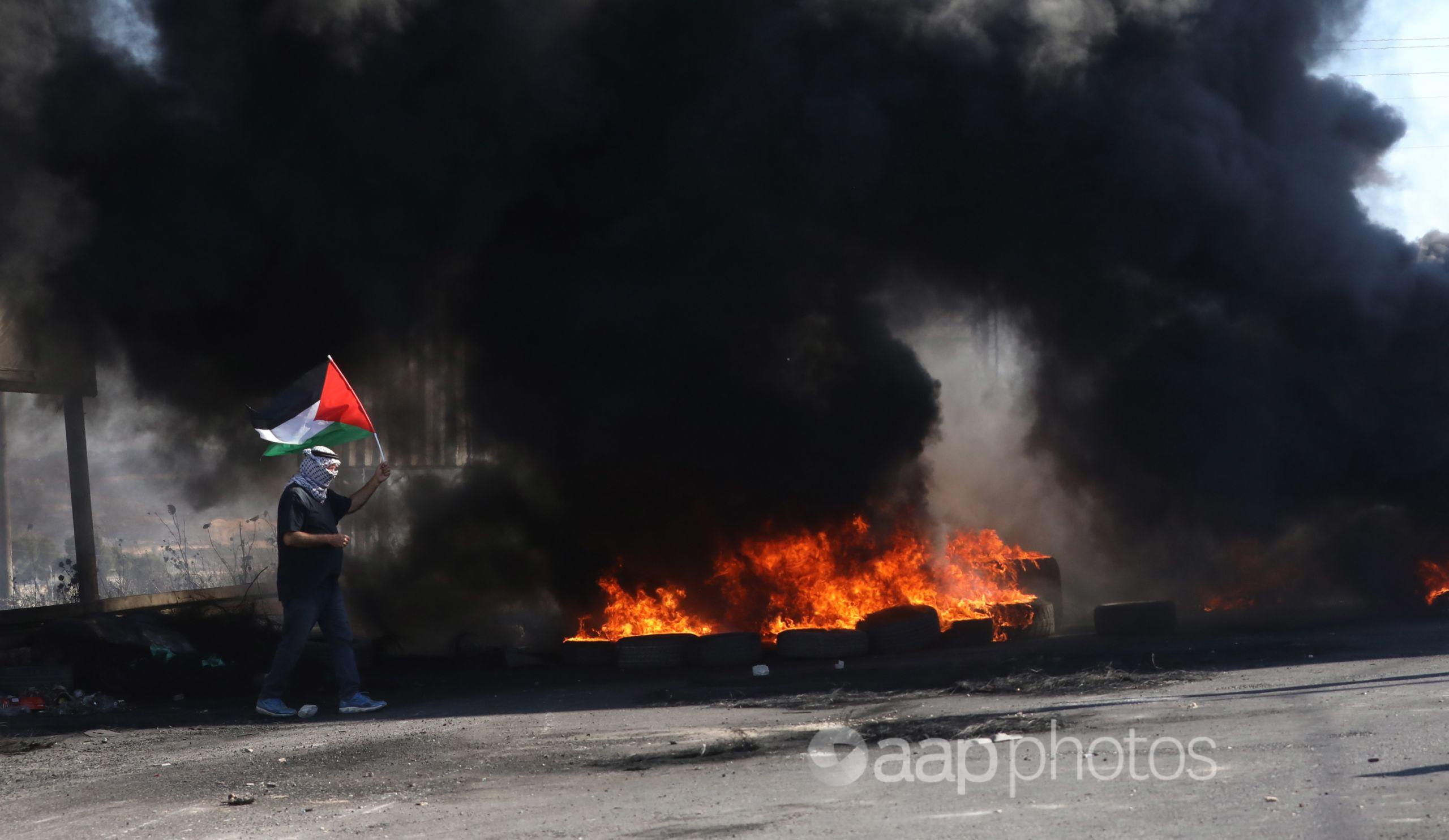 A protester waves Palestine's flag during clashes with Israeli troops