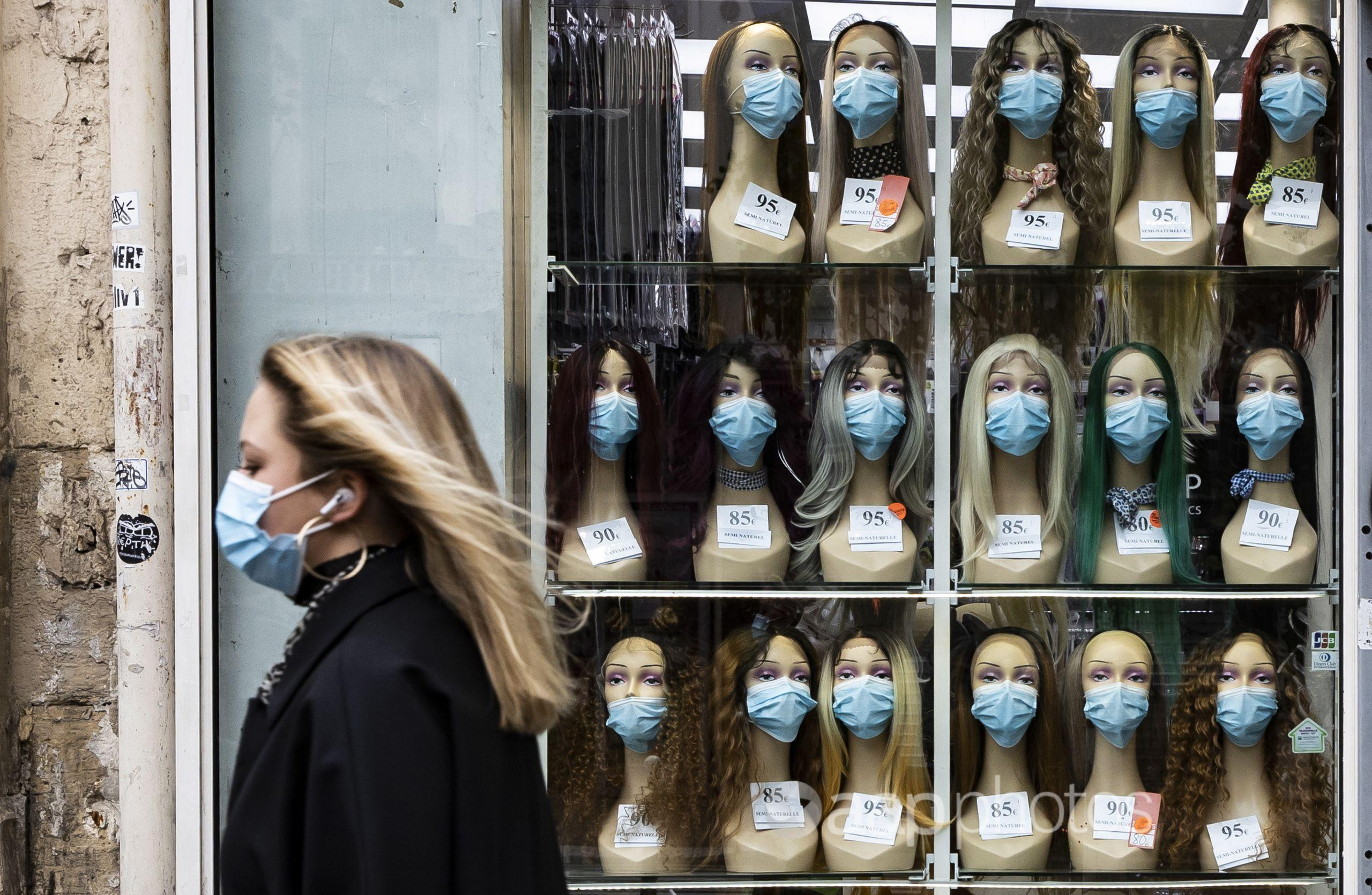 A woman wearing a face mask walks past a shop displaying masks