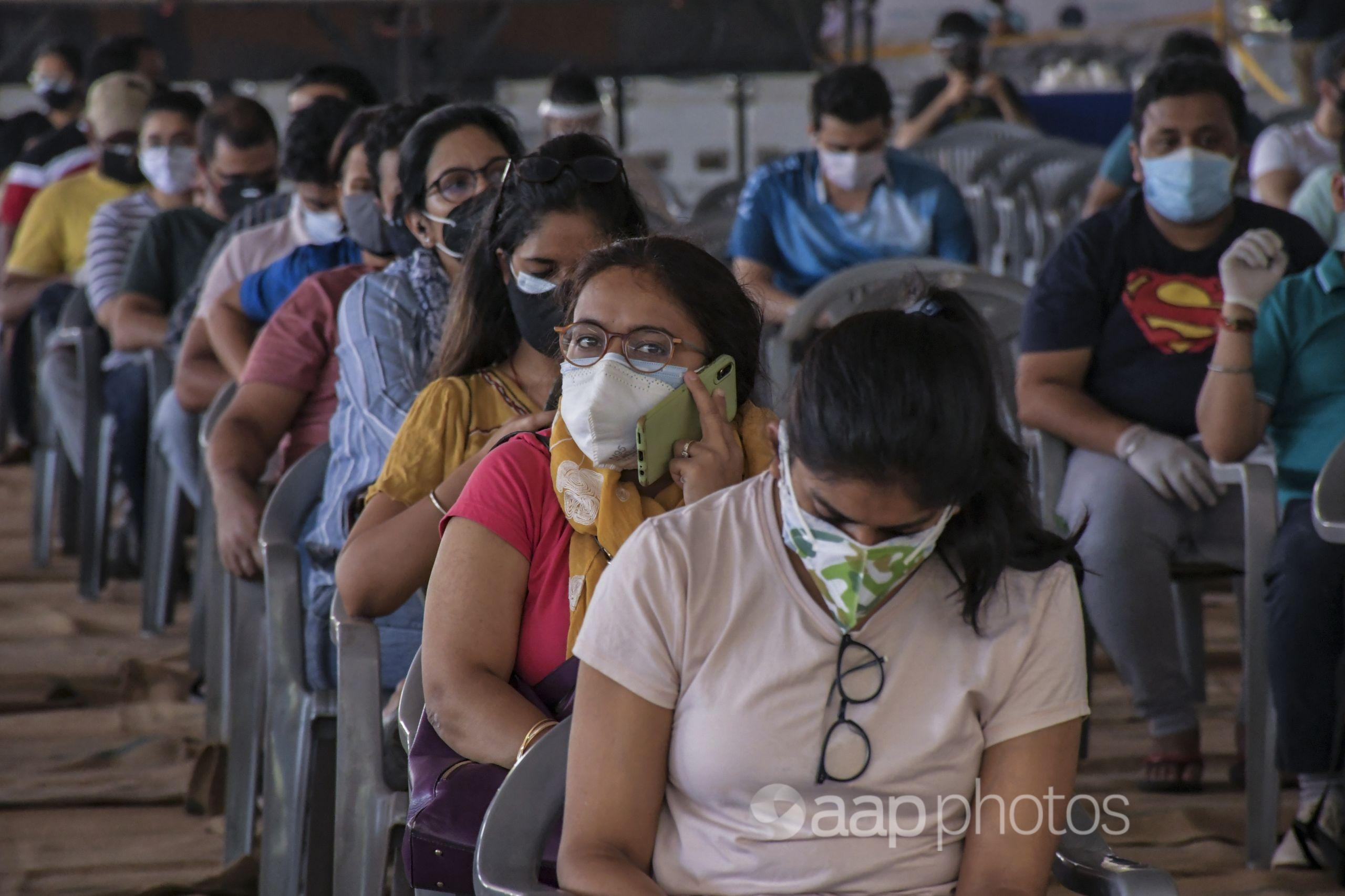 People wait to be vaccinated against the coronavirus in New Delhi.