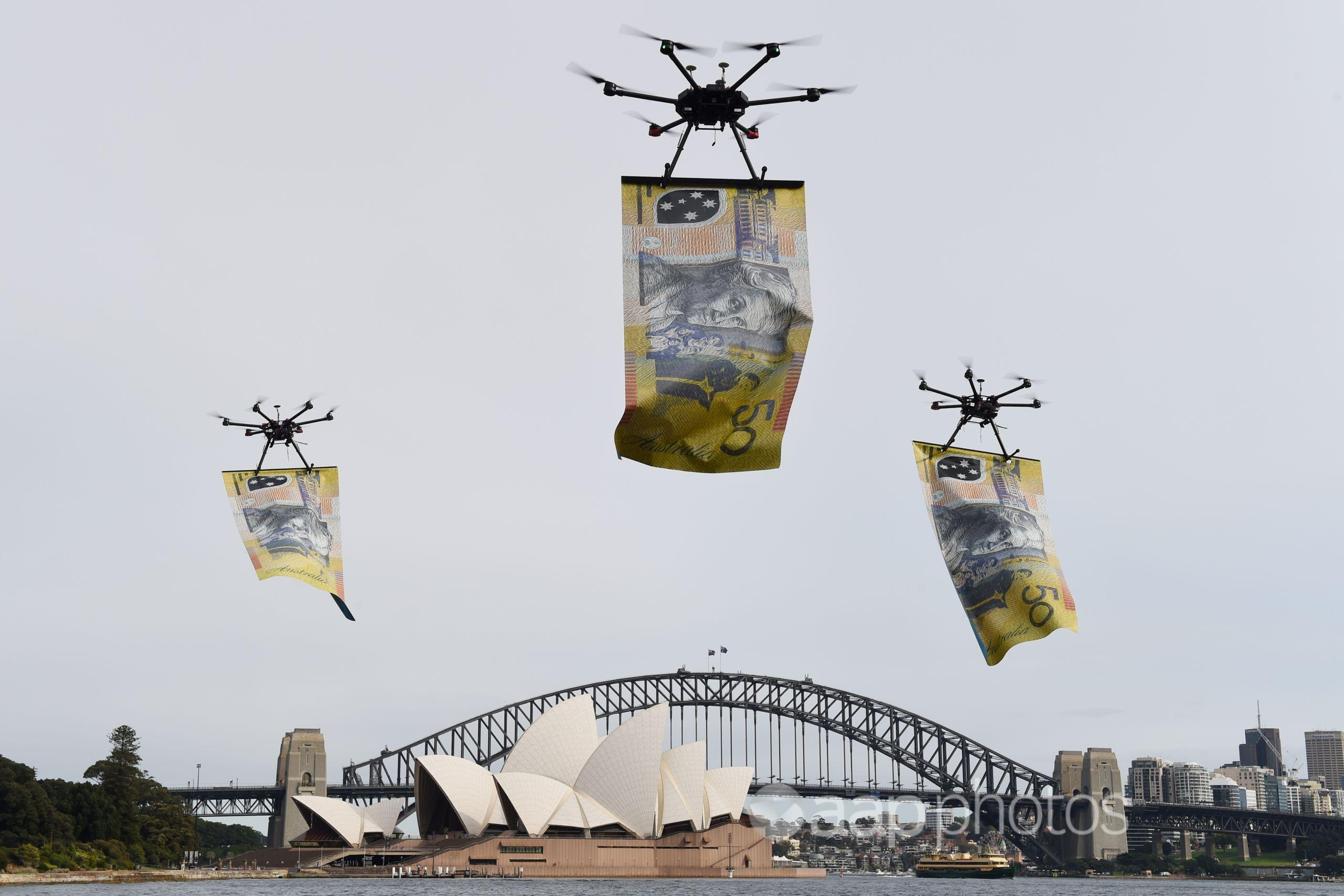 Drones carrying giant  notes are flown over Sydney Harbour.