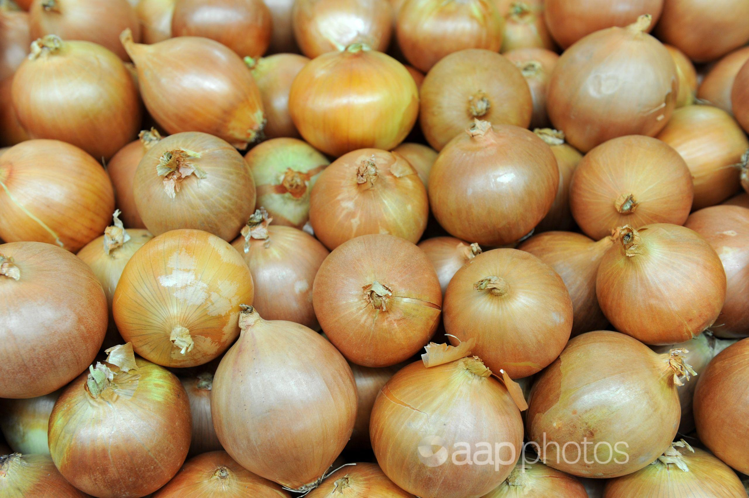 White onions sit on a stall at a store.
