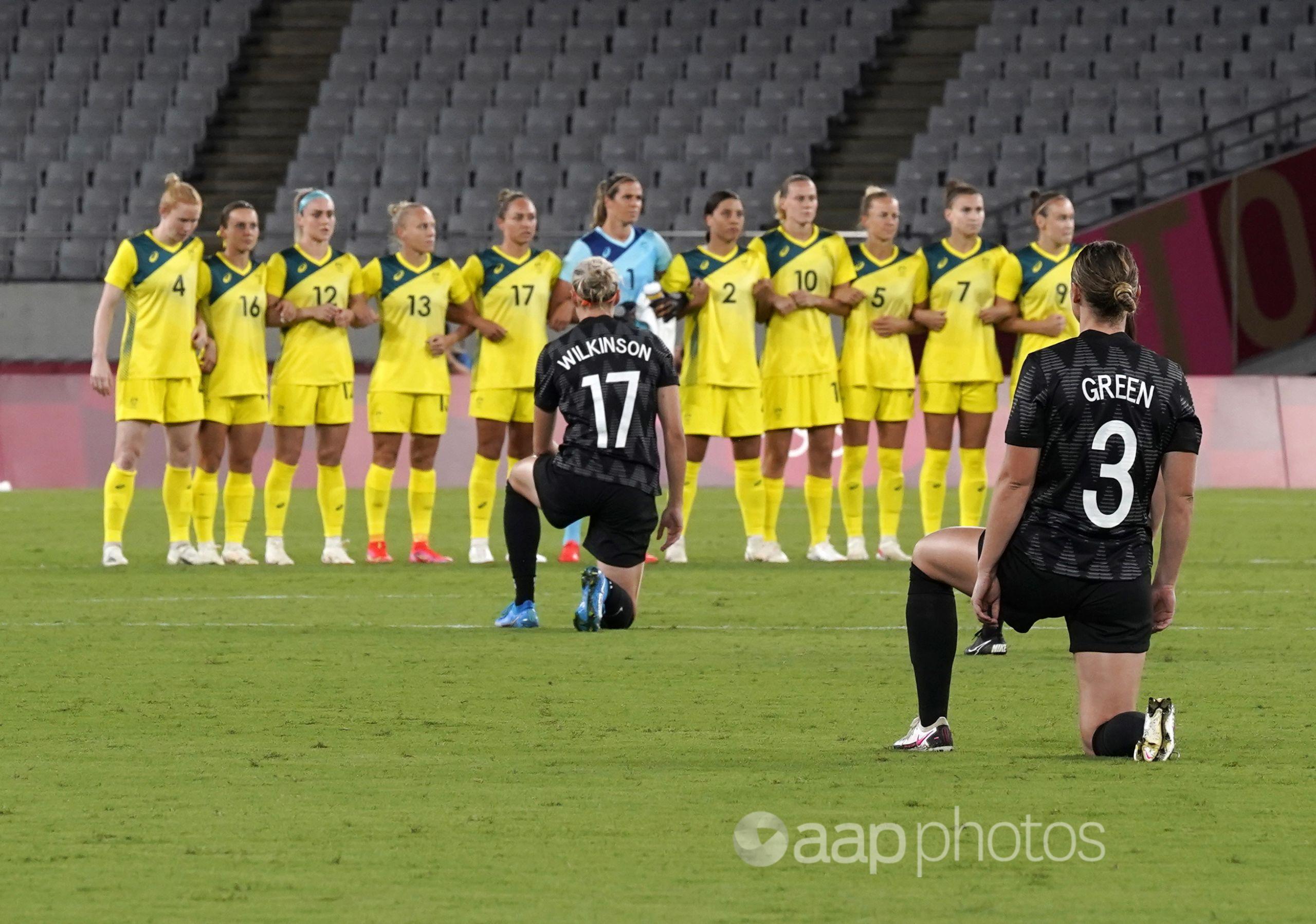 NZ players kneel before the women's soccer match against Australia.