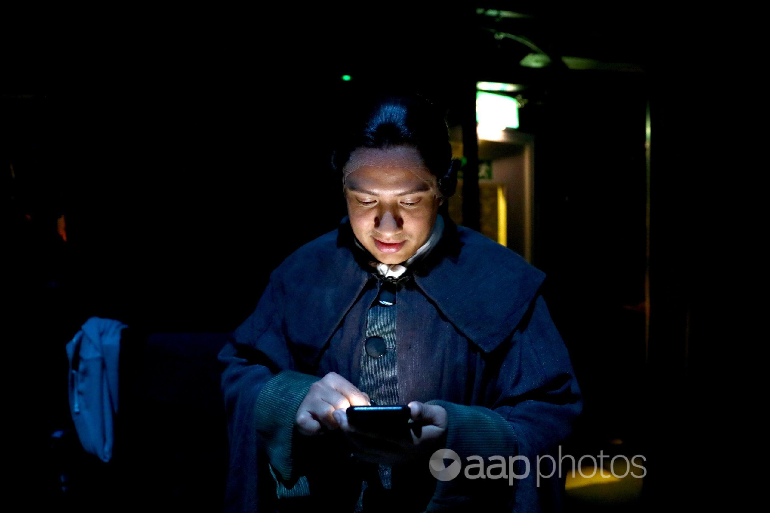 A man checks his mobile phone.