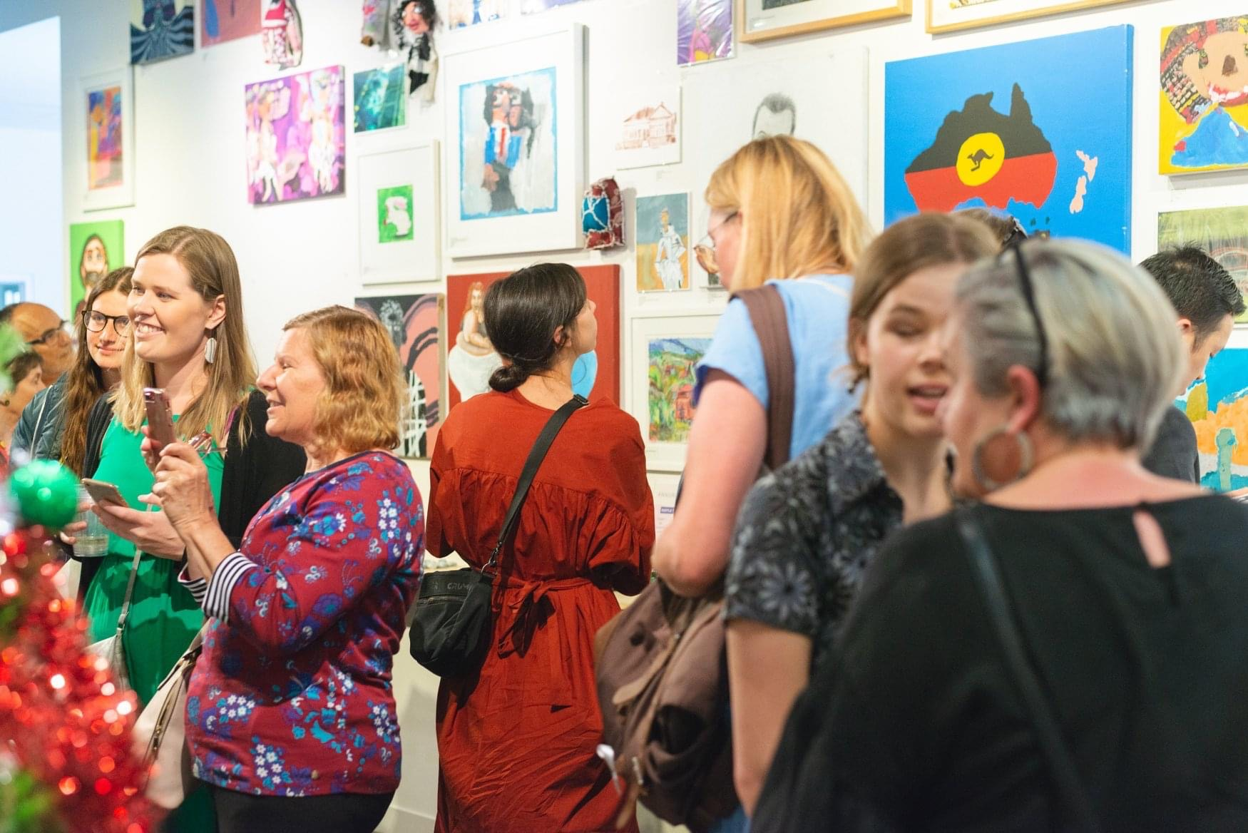 Crowd of people looking at art at a gallery