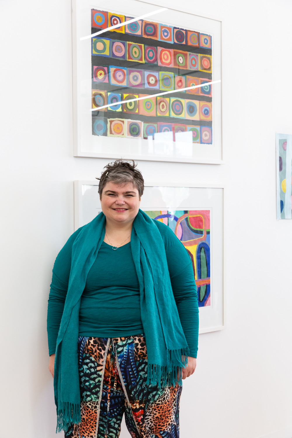 Artist Monica Lazzari stands in front of her colourful artwork