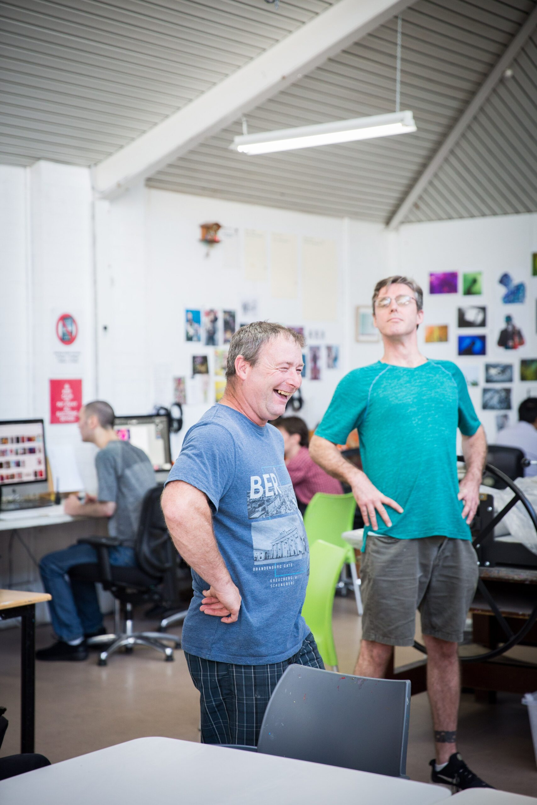 Two middle age men wearing blue shirts laugh together in art studio