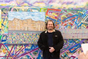 James MacSporran stands in front of his colourful wall mural and artwork on canvas