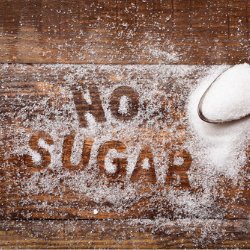 "The words ""No Sugar"" written on a table from spilt sugar"