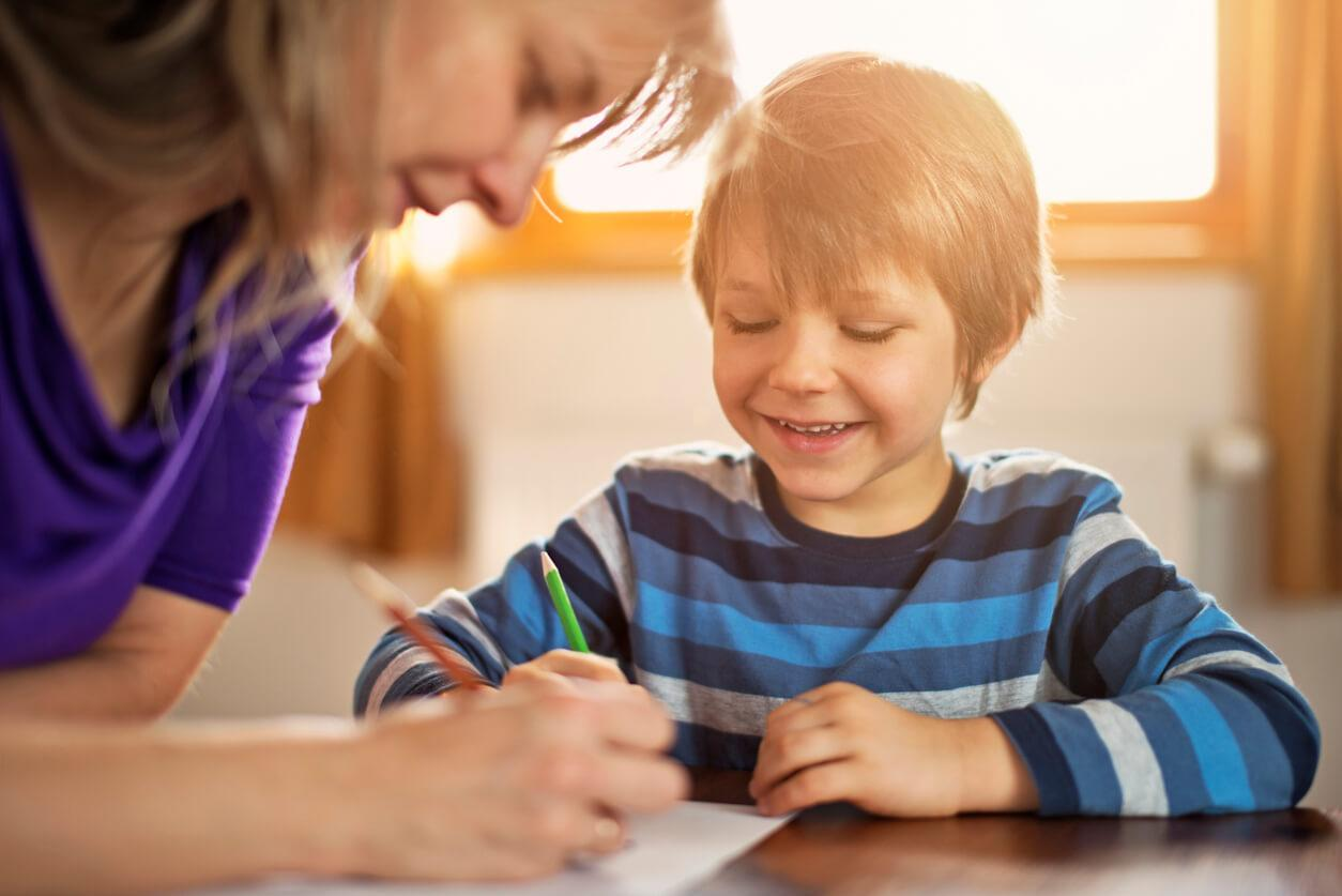 Young boy drawing at table with parent