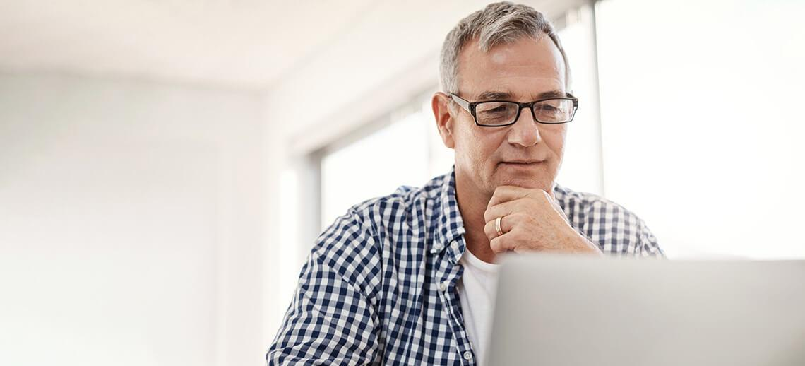 A manager sitting working on his laptop