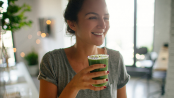 A woman enjoying a glass of green juice