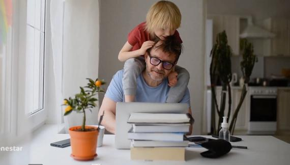 A dad trying to work from home while his young son sits on his shoulders
