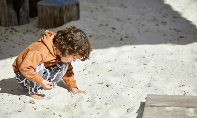 Young boy in sandpit looking through sand