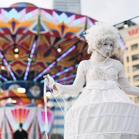 A Fringe Festival performer in front of a ride at Elizabeth Quay