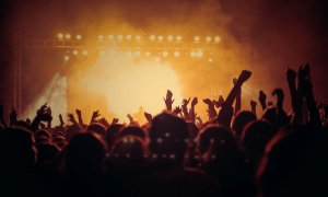 A backlit shot of a crowd with their hands raised facing a concert stage.