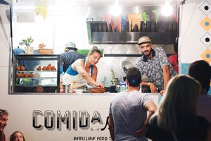 People serving customers at Comida food truck