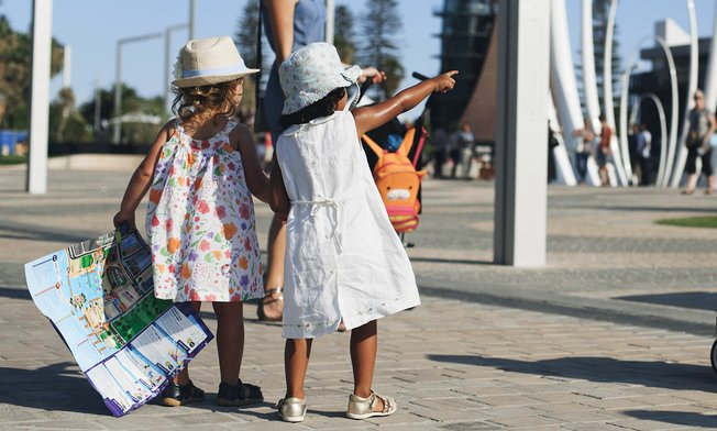 Two young girls pointing and holding a map at Elizabeth Quay