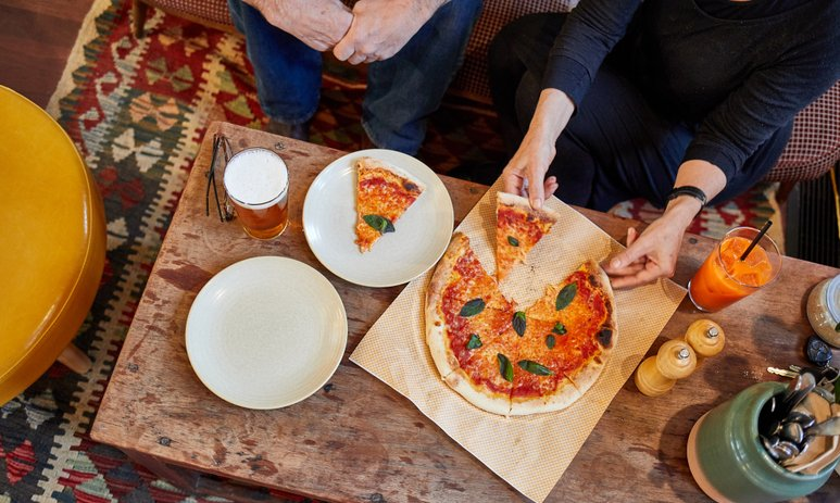 An aerial view of a pizza, pint of beer and orange juice on a wooden table.