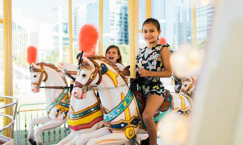 Two girls on the Elizabeth Quay Carousel horses