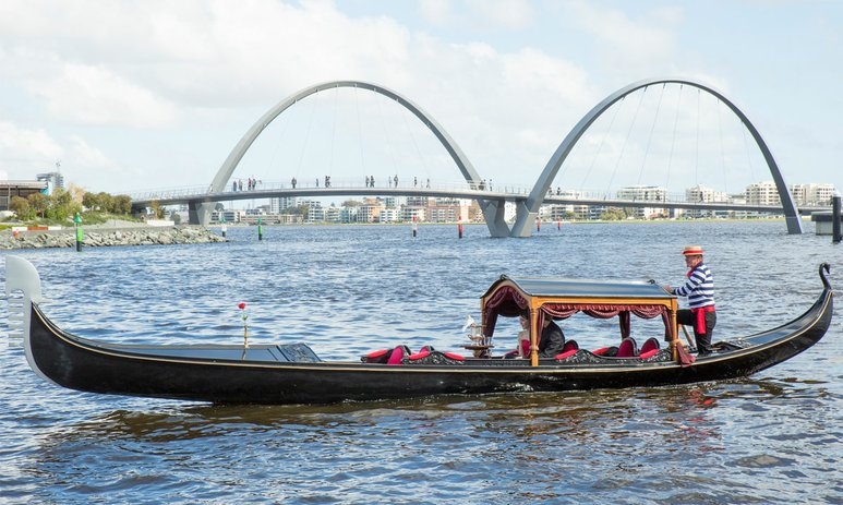 Gondola with 2 passengers cruising in Elizabeth Quay with the bridge in the background