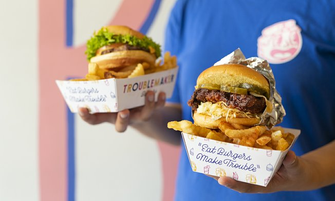 burgers and fries held in paper plates