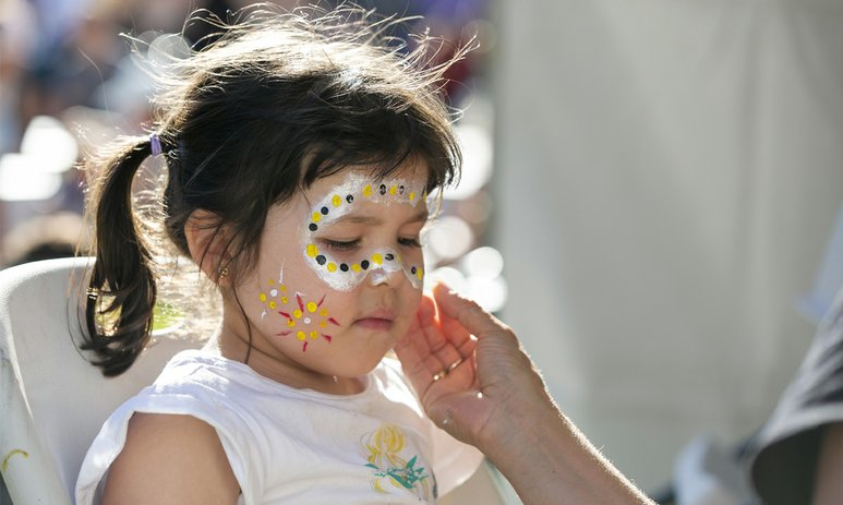 A little girl with pigtails getting her face painted