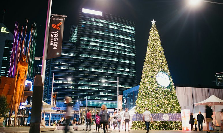 People walking through Yagan Square past a Christmas tree lit up with 46,000 sparkling lights.