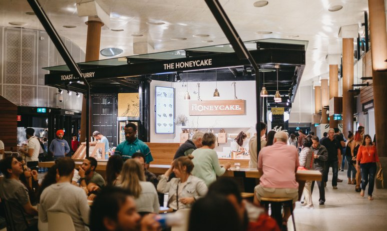 The interior of the Yagan Square Market Hall as people walk through and sit down to dine.