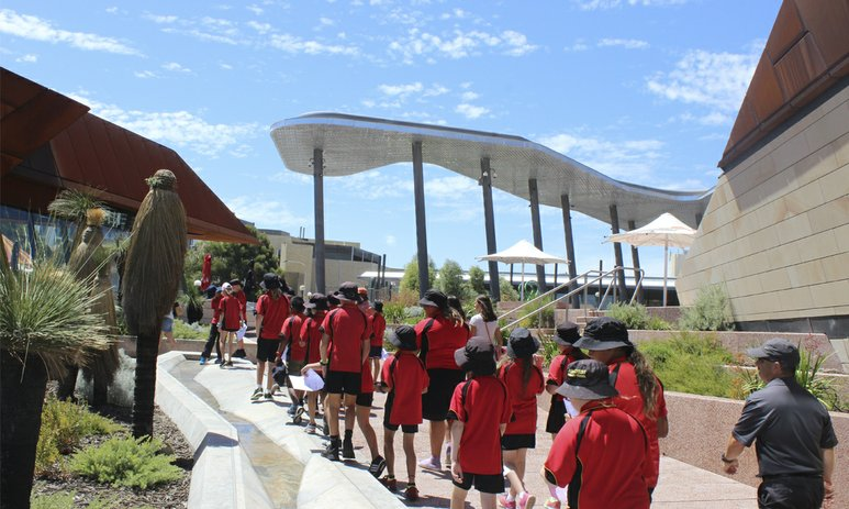 An image of school students walking through Yagan Square up towards the amphitheatre during the day