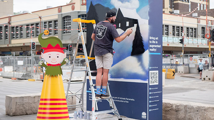 Man paints a mural in the middle of Parramatta town centre.