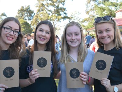 4 young women holding a youth publication that they have edited.
