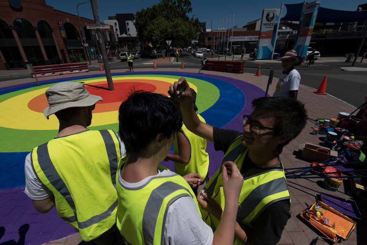 People painting the rainbow roundabout