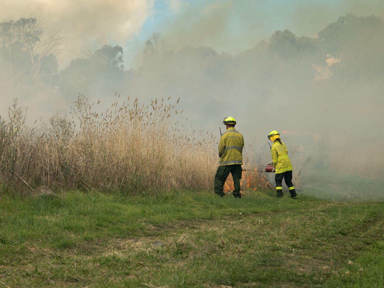 Two rangers lighting a fire in long grass