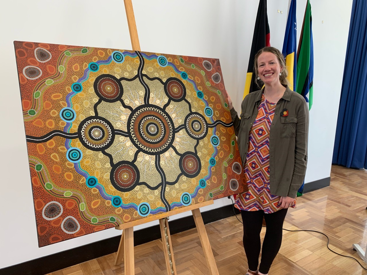 Artist Leah Brideson with her artwork titled 'Strength in Community' commissioned for the ACT Aboriginal and Torres Strait Islander Agreement 2019-2028